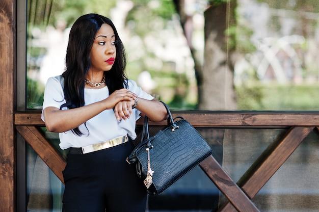 Stilvolle afroamerikanergeschäftsfrau mit handtasche auf straßen der stadt und betrachten von uhren.