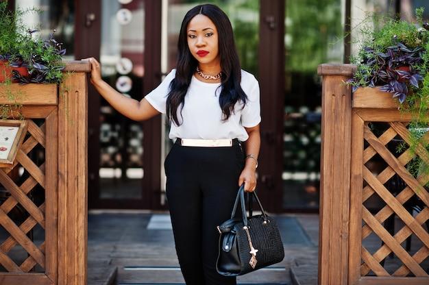 Stilvolle afroamerikanergeschäftsfrau mit handtasche auf straßen der stadt.