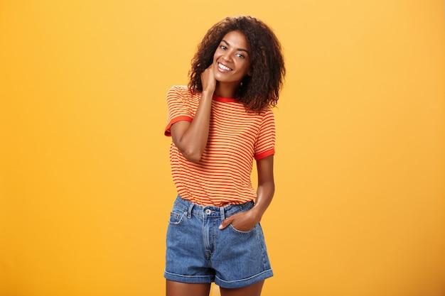 Stilvolle afroamerikanische schlanke frau mit dem lockigen mittleren haar, das hand in den jeansshorts kippenden kopf hält.