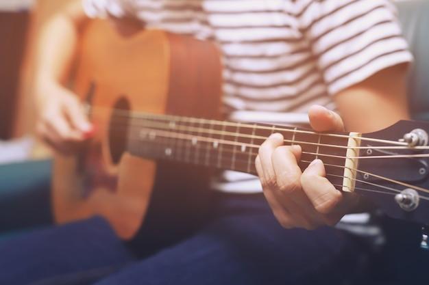 Stilvolle akustikgitarre spielen von hand.