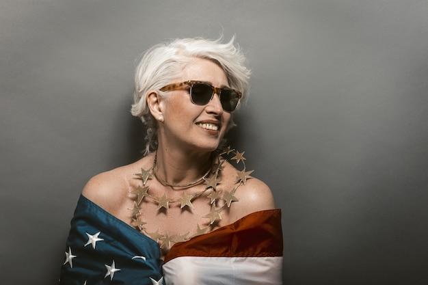 Stilvolle amerikanische frau, die usa-flagge trägt. reife frau in der sonnenbrille zahnig lächelnd
