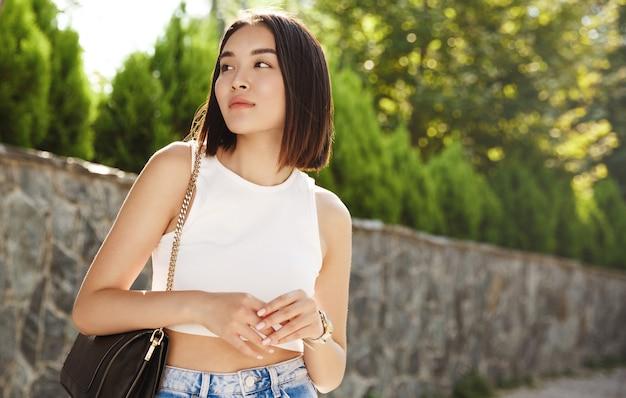 Stilvolle asiatische frau, die auf jemanden im park wartet