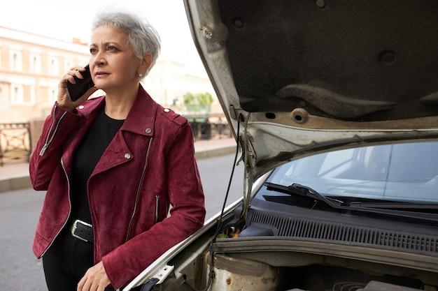 Stilvolle attraktive grauhaarige reife fahrerin, die nahe ihrem gebrochenen weißen auto mit offener motorhaube steht und am telefon spricht