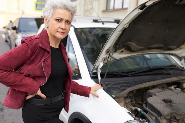 Stilvolle attraktive grauhaarige reife fahrerin, die nahe ihrem gebrochenen weißen auto mit offener motorhaube steht