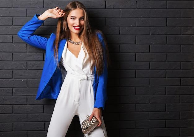 Stilvolle attraktive junge frau im lässigen weißen kostüm und in der blauen jacke, die luxusgeldbörse hält