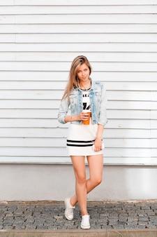 Stilvolle attraktive junge frau in einem sportlichen weißen stilvollen kleid in der sommer-jeansjacke in den weißen turnschuhen, die nahe einem weißen holzgebäude in der stadt aufwerfen. nettes mädchen, das ein süßes getränk trinkt.