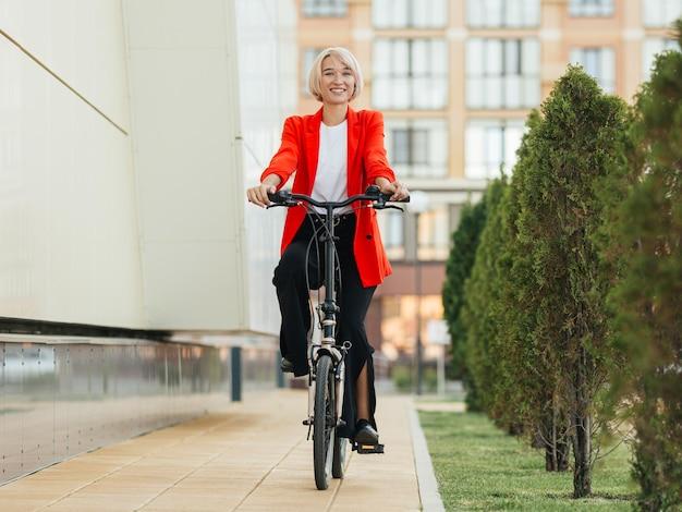 Stilvolle blonde frau, die ihr fahrrad reitet