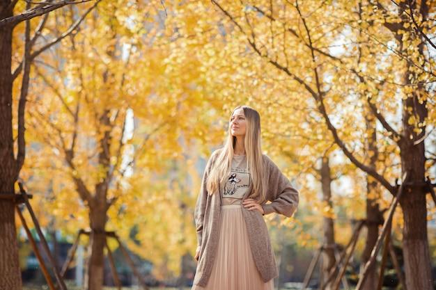Stilvolle blonde frau im herbstlichen park