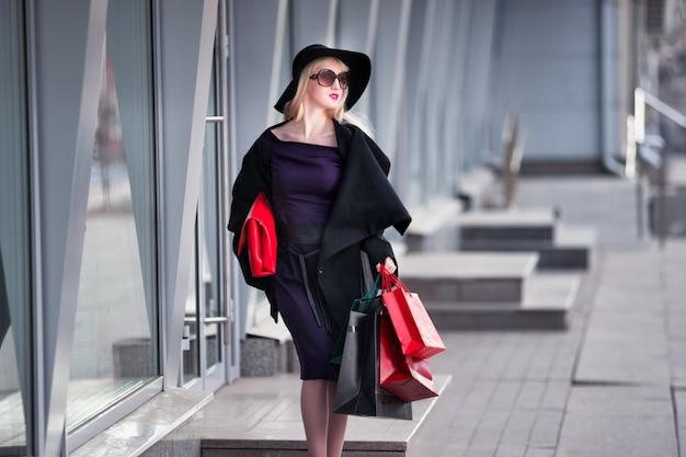Stilvolle blonde frau im schwarzen mantel, in der sonnenbrille und im hut mit einkaufstaschen geht entlang der straße, feiertagskonzert