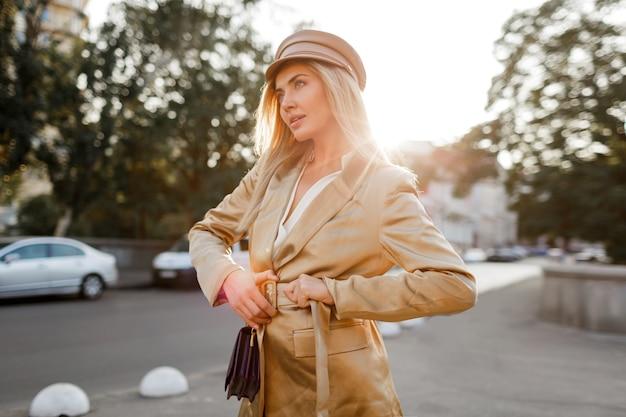 Stilvolle blonde frau in beiger mütze und jacke, die auf der straße gehen. herbst look. sonnenuntergangslicht. elegante geldbörse.