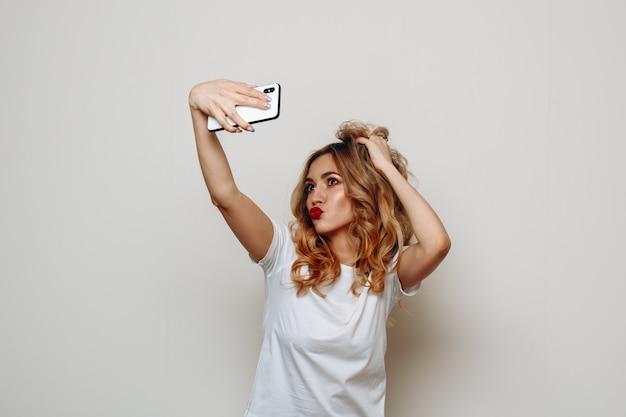 Stilvolle blonde frau mit roten lippen nimmt selfie auf smartphone auf weiß.