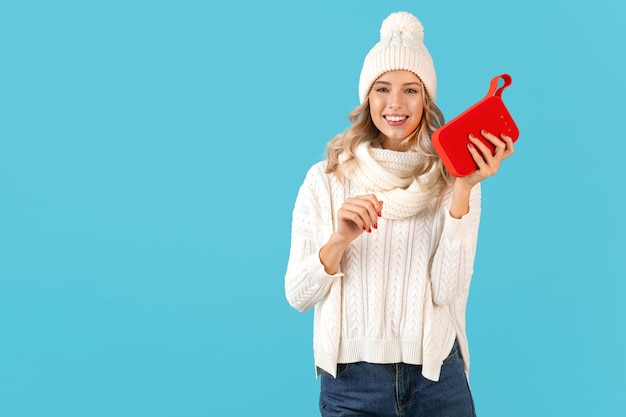 Stilvolle blonde lächelnde schöne junge frau, die drahtlosen lautsprecher hält, der das glückliche tanzen der musik beim tragen des weißen pullovers und der strickmütze winterstilmode hört, die lokal auf blauer wand aufwirft