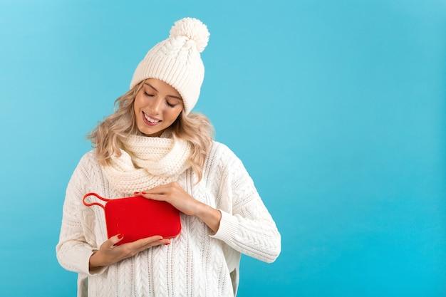 Stilvolle blonde lächelnde schöne junge frau, die drahtlosen lautsprecher hält, der musik hört, die glücklich weißen pullover und strickmütze trägt, die auf blau aufwirft