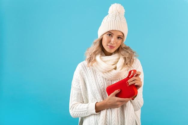Stilvolle blonde lächelnde schöne junge frau, die drahtlosen lautsprecher hält, der musik hört, die glücklich weißen pullover und strickmütze winterart mode trägt, die lokal auf blauer wand posiert