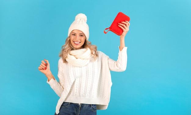 Stilvolle blonde lächelnde schöne junge frau, die drahtlosen lautsprecher hält, der musik trägt, die weißen pullover und strickmütze trägt, die auf blau aufwirft