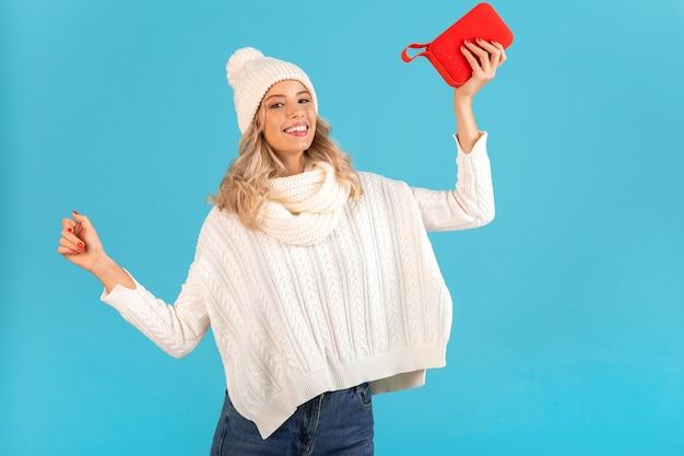 Stilvolle blonde lächelnde schöne junge frau, die einen drahtlosen lautsprecher hält, der musik hört, die glückliches tanzen mit weißem pullover und strickmütze im winterstil-mode posiert