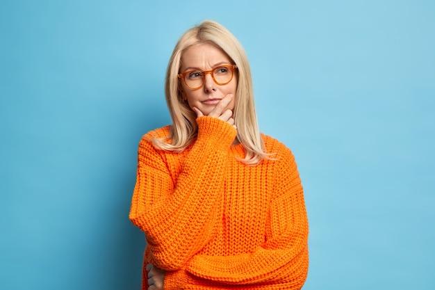 Stilvolle blonde runzlige frau denkt tief über etwas nach, das kinn hält, trägt eine brille und strickt einen orangefarbenen pullover.