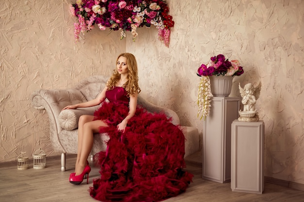 Stilvolle blonde schöne frau auf dem sofa im burgunderfarbenen kleid
