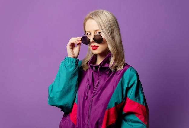 Stilvolle blondine in windjacke der 80er jahre und runde sonnenbrille auf lila wand