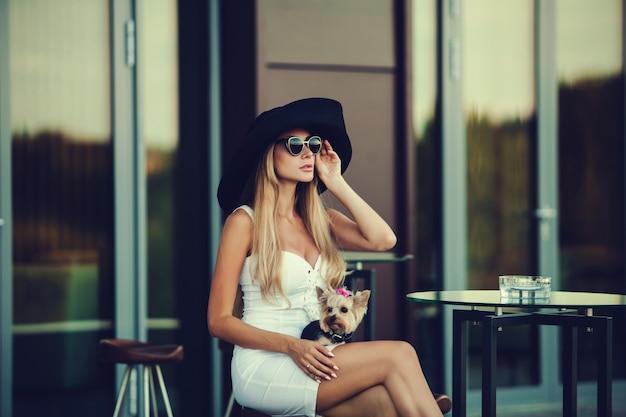Stilvolle blondine mit yorkshire terrier