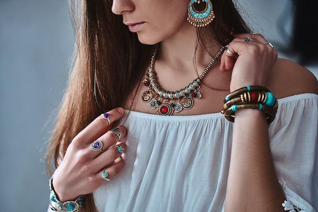 Stilvolle boho-chic-frau mit weißer bluse, ohrringen, armband, goldener halskette und silbernen ringen. modisches indisches hippie-zigeuner-bohemien-outfit mit schmuckdetails
