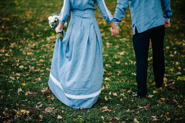 Stilvolle brautfrau im bestickten kleid und im bräutigam im hemd hält hochzeitsstraußblumen. hochzeitszeremonie.