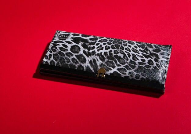Stilvolle brieftasche auf rot. modischer minimalismus.