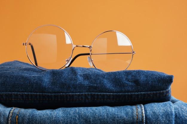 Stilvolle brille auf einem stapel jeans auf braunem hintergrund brille mit modischem rundem metallrahmen