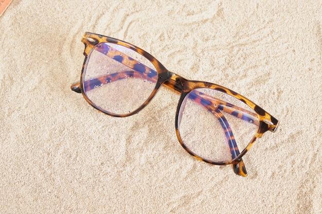 Stilvolle brille mit gefleckten kunststoffrahmen auf dem sand, draufsicht des kopierraums