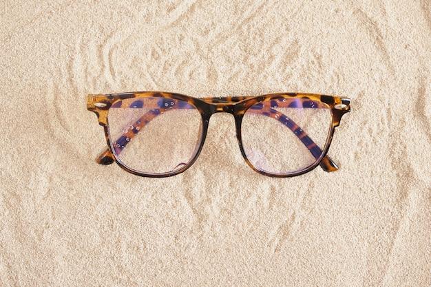 Stilvolle brille mit gefleckten kunststoffrahmen auf dem sand, kopierraum