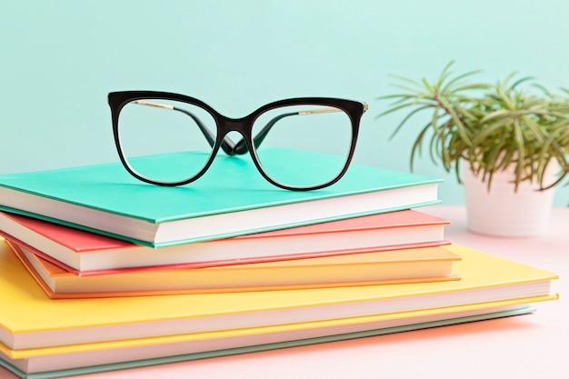 Stilvolle brille über stapel bücher. studieren, lesen, optikgeschäft, sehtest, sichtprüfung beim optiker, modeaccessoire-konzept. vorderansicht