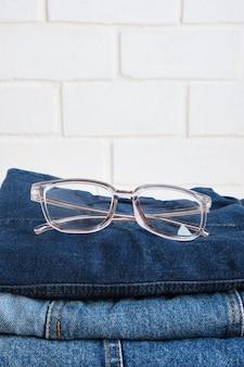 Stilvolle brillen auf einem stapel jeans auf backsteinmauerhintergrundkopienraum