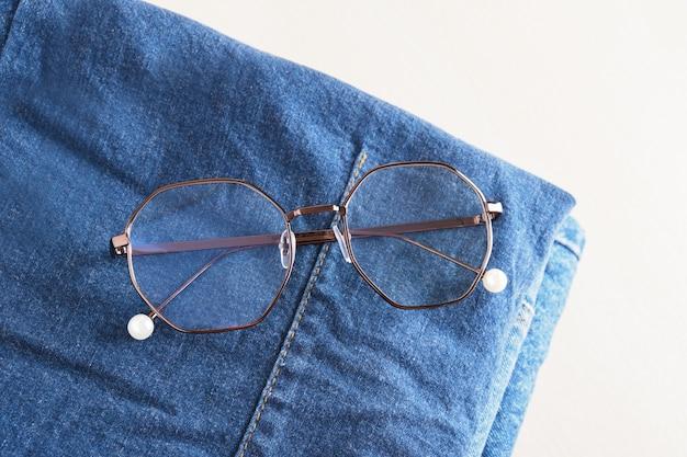 Stilvolle brillen auf einem stapel jeans auf hölzernem hintergrund kopienraum draufsicht