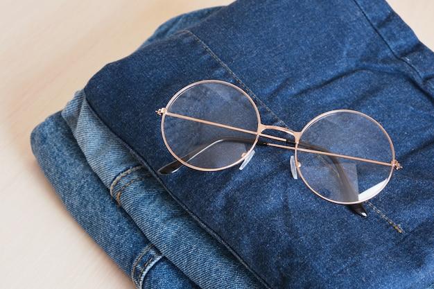 Stilvolle brillen auf einem stapel jeans auf holzhintergrund kopienraum draufsicht brillen mit modischem runden metallrahmen