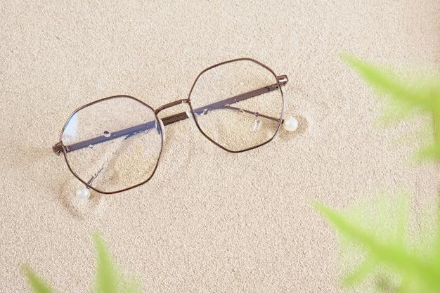 Stilvolle brillen in einem runden metallrahmen auf der draufsicht des sandkopierraums