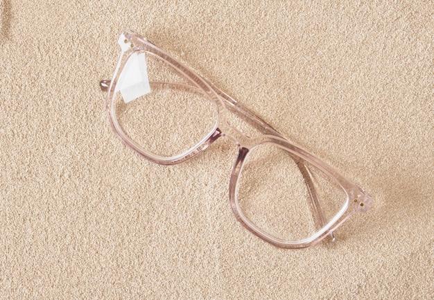 Stilvolle brillen in einem transparenten kunststoffrahmen auf dem kopienraum mit sanddraufsicht