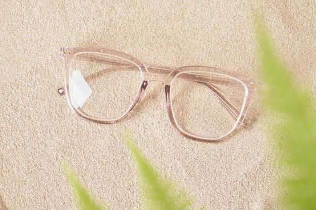 Stilvolle brillen in einem transparenten kunststoffrahmen auf dem sand, farnblätter in einem verschwommenen kopierraum