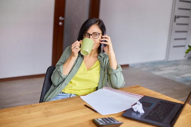 Stilvolle brünette frau in brille, die am holztisch mit notizblock sitzt und telefoniert, tee am modernen arbeitsplatz trinkt, freiberufler, der zu hause arbeitet. kaffeepause im büro sitzen, ruhezeit