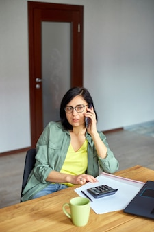 Stilvolle brünette frau mit brille, die mit notizblock am tisch sitzt und telefoniert