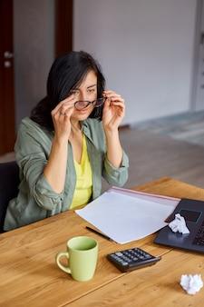 Stilvolle brünette geschäftsfrau nimmt brille ab, die am modernen arbeitsplatz arbeitet