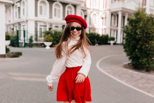 Stilvolle charmante französin in rotem rock und französischer baskenmütze