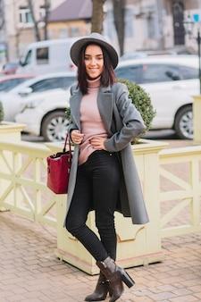 Stilvolle charmante junge frau im grauen mantel, hut mit roter tasche, die auf straße im stadtzentrum geht. brünettes haar, elegante frau, modisches modell, lächelnd, fröhliche stimmung.