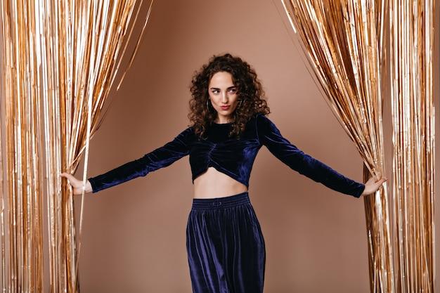 Stilvolle dame im dunkelblauen samt-outfit, das auf goldhintergrund aufwirft