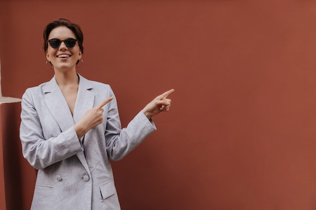 Stilvolle dame im grauen anzug und in der sonnenbrille, die zum platz für text zeigen. fröhliche kurzhaarige frau in übergroßer jacke lächelt weit draußen