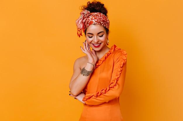 Stilvolle dame im orangefarbenen kleid und im hellen verband auf ihrem kopf mit schüchternem lächeln schaut auf orange raum herab.