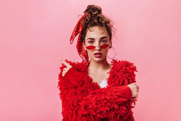 Stilvolle dame im roten outfit und in den gläsern, die auf rosa hintergrund aufwerfen