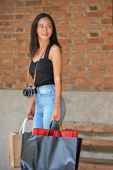Stilvolle dame im sommer in der stadt spazieren und einkaufen in der stadtstraße mit retro-kamera und einkaufstaschen