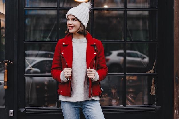 Stilvolle dame in guter stimmung lehnte sich an fenster mit schwarzem holzrahmen. mädchen gekleidet in jeans, hut und rote jacke posierend.