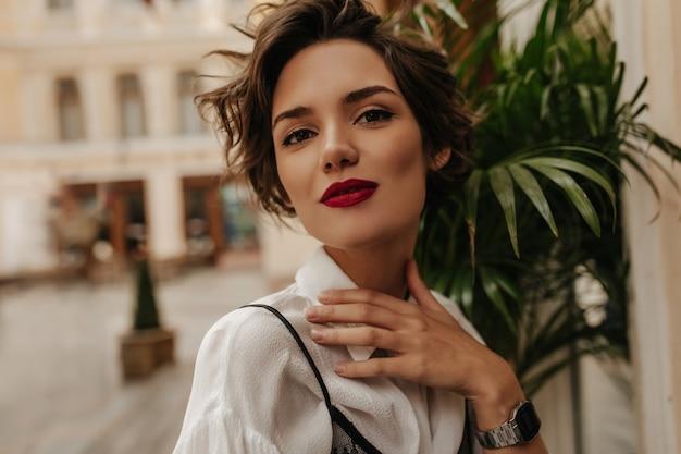 Stilvolle dame mit kurzer frisur im hellen hemd, das im café lächelt. brünette frau mit rotem lippenstift im restaurant.
