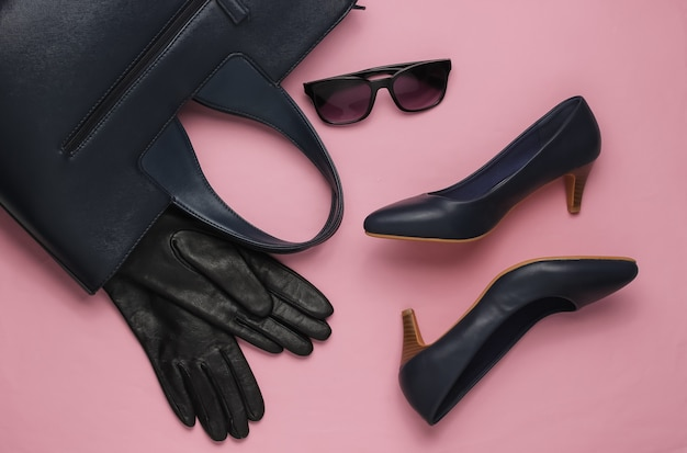 Stilvolle damen accessoires und schuhe auf rosa pastell hintergrund leder high heel schuhe tasche sonnenbrille handschuhe draufsicht